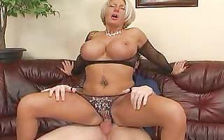 breasty older blond in black fishnet brassiere